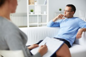 Pensive man trying to relax on sofa during psychological therapy